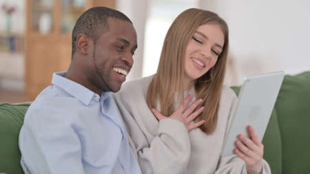Online Video Call on Tablet by Interracial Couple at Home