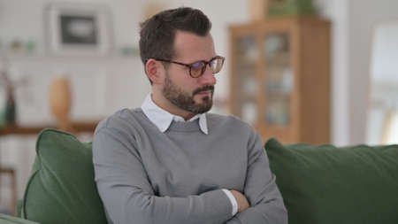 Middle Aged Man Feeling Worried while Thinking on Sofa