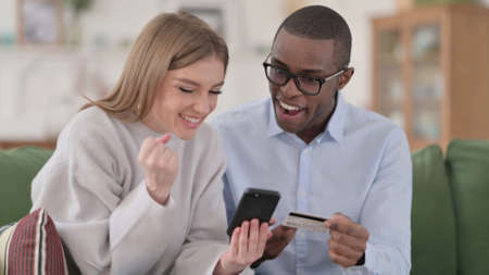 Interracial Couple making Online Shopping Payment on Smartphone