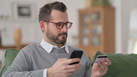 Middle Aged Man making Online Payment on Smartphone