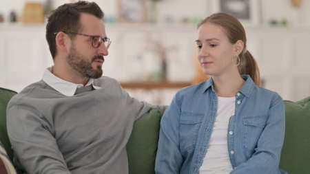 Happy Couple having Conversation while Sitting on Sofa