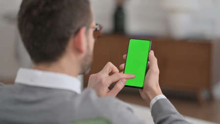 Man Using Smartphone with Chroma Key Screen at Home