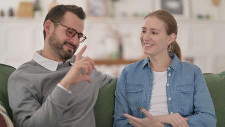 Couple having Conversation while Sitting on Sofa 스톡 콘텐츠