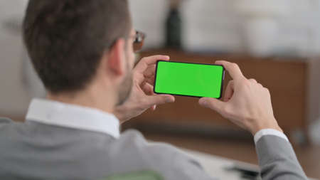 Man Watching Smartphone with Chroma Key Screen at home
