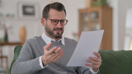 Middle Aged Man having Loss while Reading Documents