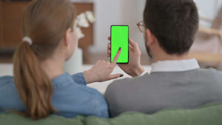 Rear View of Couple using Smartphone with Green Chroma Key Screen 스톡 콘텐츠