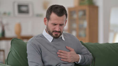 Middle Aged Man having Sudden Pain in Heart on Sofa