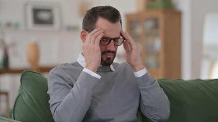 Middle Aged Man having Headache Sitting on Sofa