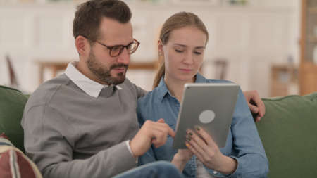 Couple using Tablet Together at Home 스톡 콘텐츠