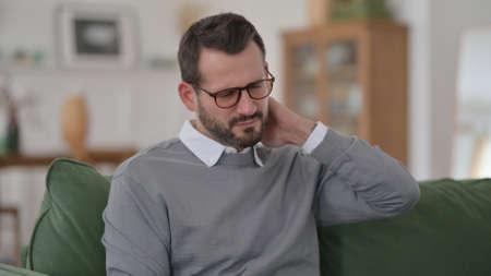 Middle Aged Man having Neck Pain on Sofa