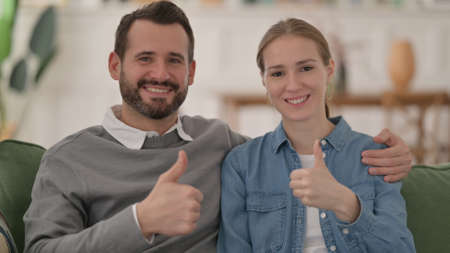 Positive Couple showing Thumbs Up while Sitting on Sofa