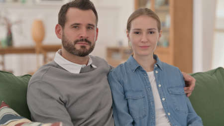 Serious Couple Looking at the Camera while Sitting on Sofa