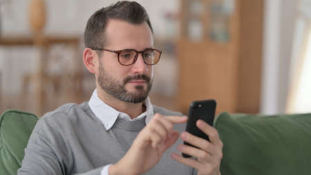 Portrait of Middle Aged Man using Smartphone on Sofa 스톡 콘텐츠