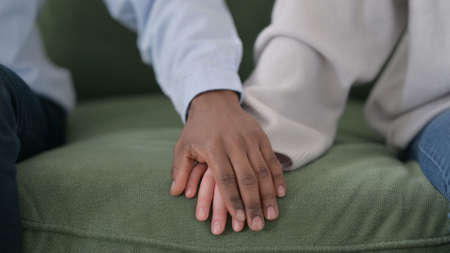 Loving African Man Putting Hand over Caucasian Womans Hand