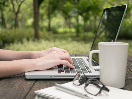 Hand of female using on computer laptop with white coffee cup on the wooden desk in the park.