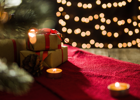 Christmas gift boxes on red scarf and candle on bokeh lights background. Stock Photo