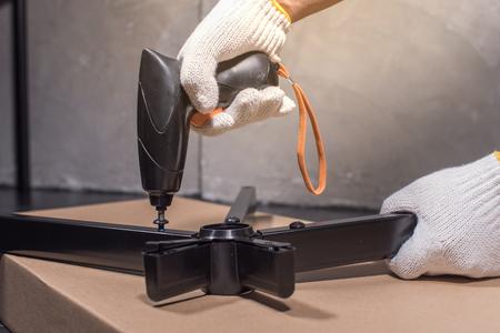 Craftsman assembling piece of revolving chair using screwdriver