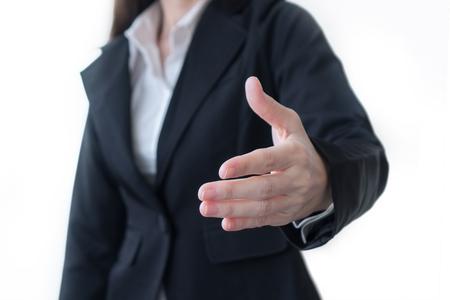 Vrouw in een pak stak haar hand uit voor een handdruk op een witte achtergrond. Stockfoto