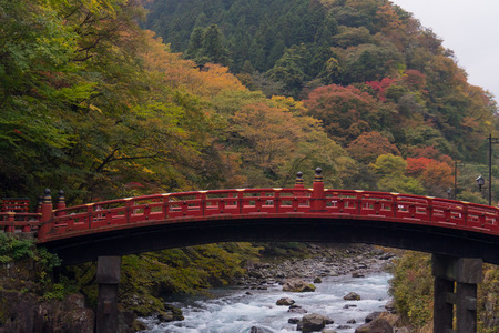 Shinkyo red bridge in autumn forest and water stream Reklamní fotografie