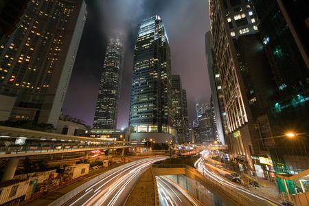 街の夜に近代的な建物とトラフィックの光の筋