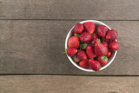 Strawberries in white bowl on wood table with copyspace. Reklamní fotografie