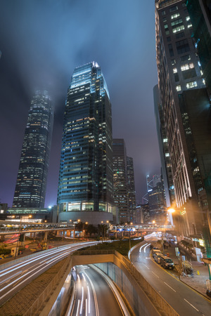 City night with traffic lights trail and business tower. Imagens