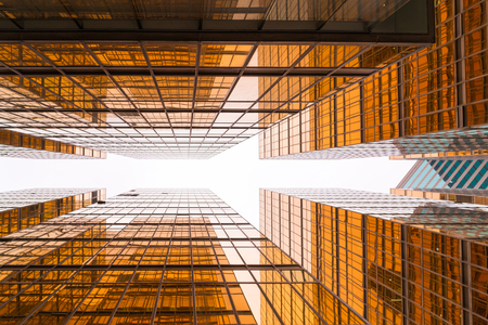 Low angle view of golden glass mirror of modern office buildings in Hong Kong.