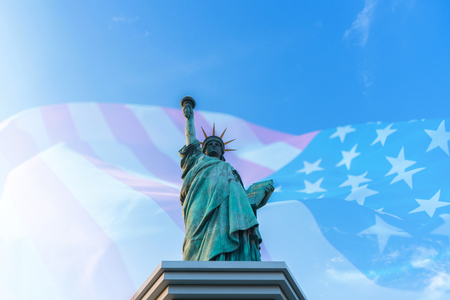 Double exposure of statue of liberty with United States of American flag.