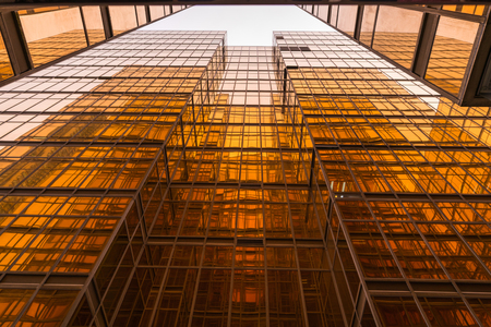 Gold glass mirror of contemporary buildings, low angle view.