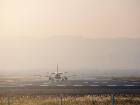 Passenger airplane on runway airport at sunset.