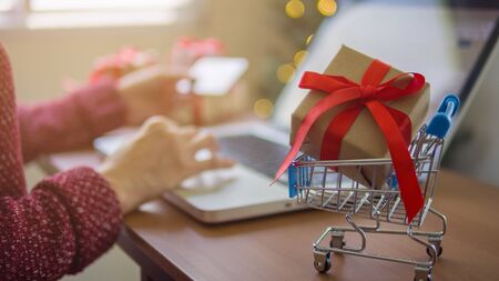 Woman using a laptop for shopping online at home in christmas day.
