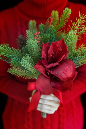 Woman wear red sweater hold christmas flower bouquet. Stock Photo