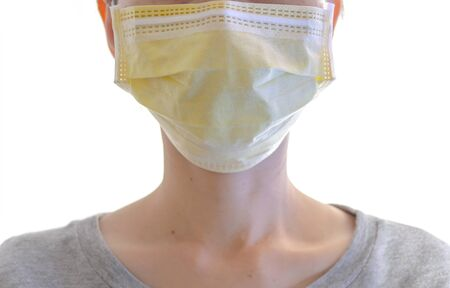 Close up of woman wearing surgical mask on her face on white for protection against contagious or covid-19 virus disease.