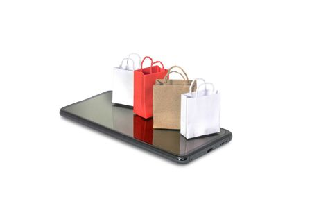 Shopping online concept with paper bags on smartphone isolated on white.