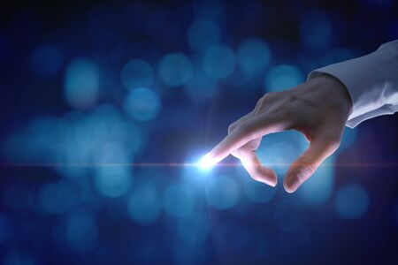 Female hand pointing with shining light on blue bokeh background.