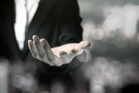 Business woman in black suit shows outstretched hand with bokeh black and white theme.
