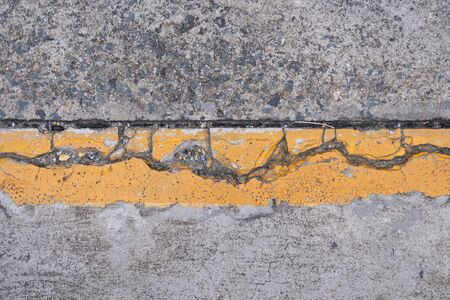 A yellow boundary line on the cracked concrete road.