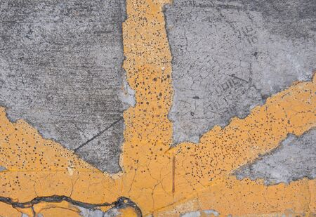 A yellow line on the cracked concrete road.
