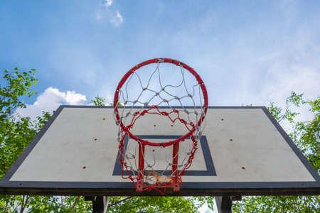 Basketball hoop in park against the blue sky.