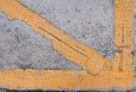 Yellow line on the cracked concrete road.