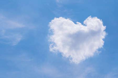 White fluffy cloud in heart shape on blue sky. Stock Photo