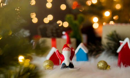 Santa claus dolls and christmas decorations against bokeh lights background.