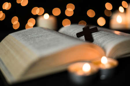 Cross on bible book and candle burning against bokeh lights background.