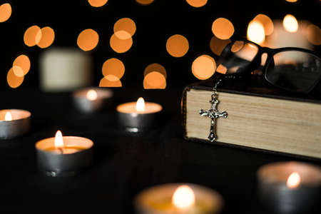 Cross rosary on bible book with candle lights against bokeh lights background. 스톡 콘텐츠