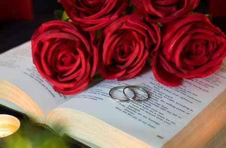 Wedding rings, red rose bouquet on open bible book for love and romance concept.