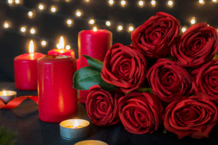 Red roses bouquet with romantic candle lights against bokeh lights for valentine day concept. Banco de Imagens