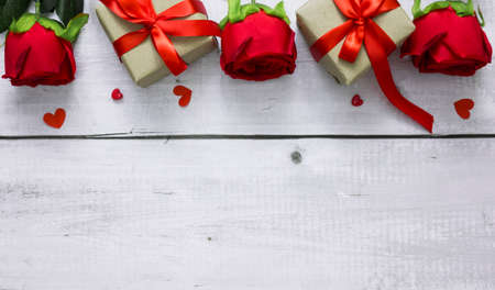 Valentine day background with red rose, hearts and gift boxes on white wood table with copyspace for text.