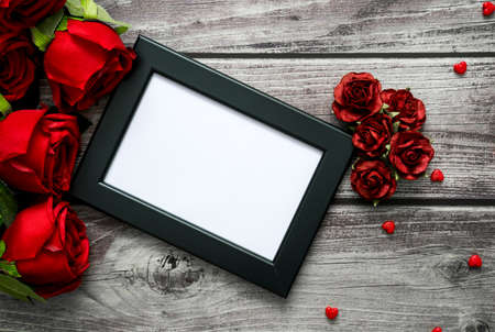 Top view of frame, red roses and heart on wooden with copyspace for Valentine, love and wedding concept.