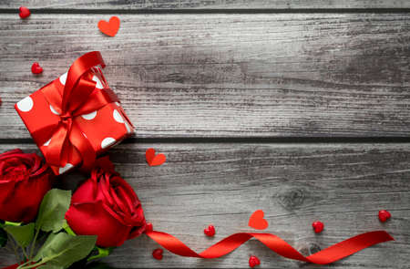 Valentine day background. Top view of rose, gift box, hearts and ribbon on wooden table with copyspace for text. Banco de Imagens