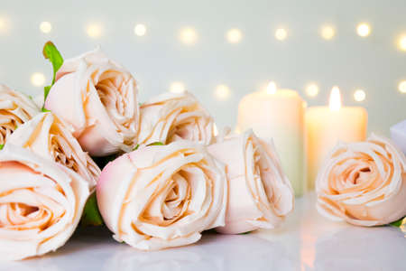 Valentine day and wedding with beige roses in pastel color, candle light in bokeh light background. Фото со стока